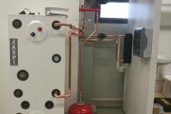 Opetuslaitteiston Ilma-vesilämpöpumppu lämmittää tai jäähdyttää Jäspin hybridivaraajaa.